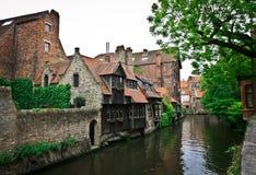 Oud huis dichtbij het kanaal in België Stock Foto's