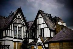 Oud huis met de daken van de brandschade Stock Afbeeldingen