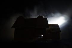 Oud huis met een Spook in de maanbeschenen nacht of Verlaten Achtervolgd Verschrikkingshuis in mist Oude mysticusvilla met surrea Royalty-vrije Stock Fotografie