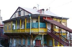 Oud huis met gesneden houten geel balkon en trap in Tbilisi, Oude Stad Stock Foto's
