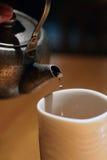 Oud ijzervee klaar om thee in een kop te gieten Stock Fotografie