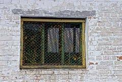 Oud ijzervenster met een rooster op een grijze bakstenen muur Stock Fotografie