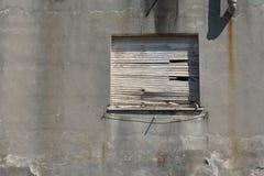 Oud ingescheept op venster in een concrete muur stock foto