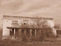 Oud isoleted de vernietigde verlaten die bouw met struiken en struiken in Sepia kleur wordt overwoekerd stock fotografie