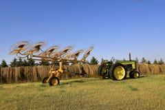 Oud John Deer 620 tractor en wielhark stock afbeelding