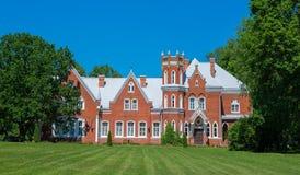 Oud kasteel van rode bakstenen met groene tuin Stock Foto