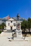 Oud kerk en standbeeld in Makarska, Kroatië stock foto