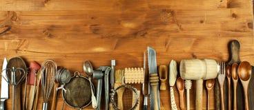 Oud keukengerei op een houten raad Verkoop van keukenmateriaal Chef-kok` s hulpmiddelen Royalty-vrije Stock Foto