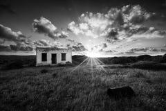 Oud klein verlaten huis op gebied met het landschap AR van de wolkenzonsondergang Stock Foto