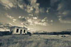 Oud klein verlaten huis op gebied met het landschap AR van de wolkenzonsondergang Stock Afbeelding