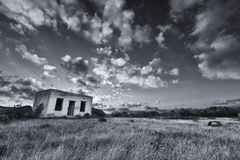 Oud klein verlaten huis op gebied met het landschap AR van de wolkenzonsondergang Royalty-vrije Stock Fotografie