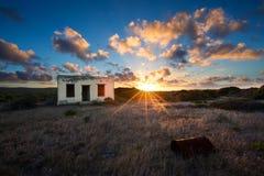 Oud klein verlaten huis op gebied met het landschap van de wolkenzonsondergang Royalty-vrije Stock Afbeelding