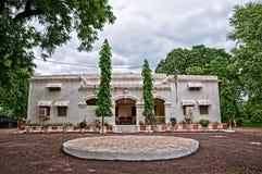 Oud koloniaal gasthuis dat door bomen wordt omringd Stock Foto's
