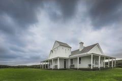 Oud landbouwbedrijfhuis op gebied met bewolkte hemel royalty-vrije stock afbeelding