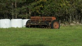 Oud landbouwwerktuig op de rand van een landbouwbedrijfgebied royalty-vrije stock afbeelding