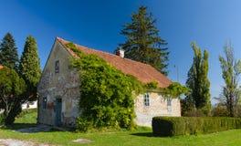 Oud landelijk die huis met groene klimop wordt overwoekerd Royalty-vrije Stock Foto