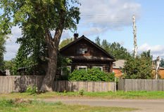 Oud logboekhuis met een grote boom vooraan Stock Afbeelding