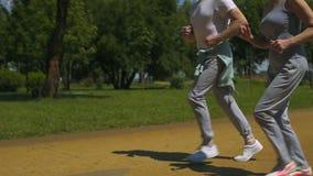 Oud mannelijk en wijfje die in park, gezonde levensstijl, slow-motion geschiktheid lopen stock footage