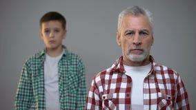 Oud mannetje die aan camera, weinig jongen kijken die, de verhoging van de pensioneringsleeftijd zich erachter bevinden stock videobeelden