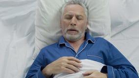 Oud mannetje die luid en in bed, het slapen problemen op oude dag snurken puffen stock afbeeldingen