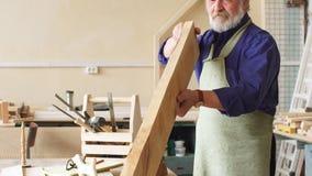 Oud mannetje in speciale kleren die planken in het inbouwen van de workshop gebruiken stock videobeelden