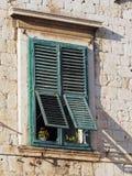 Oud mediterraan venster met groene blinden Royalty-vrije Stock Afbeelding