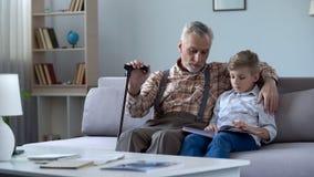 Oud mens het letten op fotoalbum met kleinzoon, die aan verhalen van de gelukkige jeugd herinneren stock afbeeldingen
