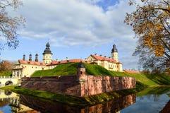 Oud, oud middeleeuws die kasteel met spiers en torens, muren van steen en baksteen door een beschermende gracht met water wordt o royalty-vrije stock foto