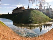 Oud, oud middeleeuws die kasteel met spiers en torens, muren van steen en baksteen door een beschermende gracht met water wordt o stock afbeelding