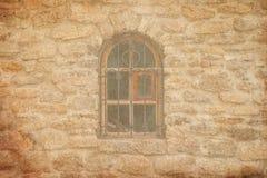 Oud middeleeuws venster met rooster in bakstenen muur stock afbeelding
