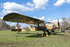 Oud militair vliegtuig op groen gras met blauwe hemel en witte wolken Royalty-vrije Stock Fotografie