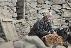 Oud Mn van de tribune van het korzokdorp voor het huis en zorgen voor zijn koeien royalty-vrije stock foto's