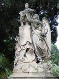 Oud monument, het broeden engel op een voetstuk met bloemen en een zeeanker stock afbeeldingen