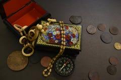 Oud muntstukken, kist, parels en kompas stock fotografie