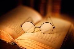 Oud open boek met glazen stock foto's