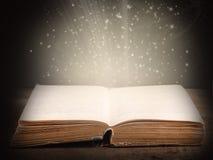 Oud open boek met magische lichte en dalende sterren Royalty-vrije Stock Foto's