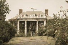 Oud overwoekerd en troosteloos verlagingshuis, stock afbeelding