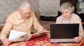 Oud paar dat heet nieuws leest Royalty-vrije Stock Foto's