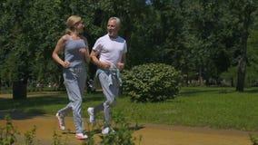 Oud paar die in park lopen en bij elkaar glimlachen, die slowmotion sport doen, stock video