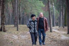 Oud paar die samen in het bos lopen die een goede tijd hebben Het glimlachen en het spreken op de herfst of de lente Stock Foto's