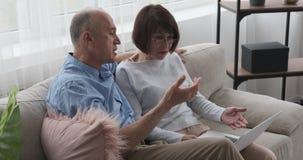 Oud paar die thuis gebruikend laptop op bank debatteren stock footage