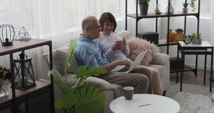 Oud paar gebruikend laptop en drinkend koffie op bank stock videobeelden