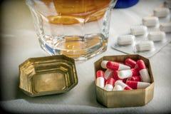 Oud pillendoosje met capsules rood en wit naast een glas water royalty-vrije stock afbeeldingen