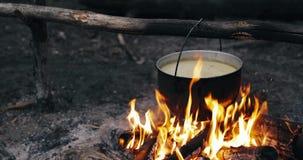 Oud Retro Kampsteelpan Gekookt Water voor Soepvoorbereiding op een Brand in Forest Flame Fire Bonfire At-de Zomeravond stock videobeelden