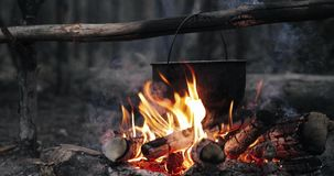 Oud Retro Kampsteelpan Gekookt Water voor Soepvoorbereiding op een Brand in Forest Flame Fire Bonfire At-de Zomeravond stock footage