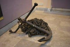 Oud roestig anker met ketting op grond stock afbeelding