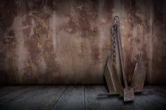 Oud roestig bootanker in pleistermuren en oude houten vloeren Royalty-vrije Stock Afbeeldingen
