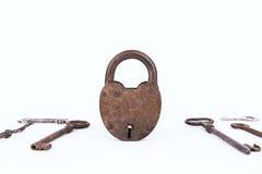 Oud roestig die hangslot met inzameling van sleutels op witte achtergrond worden geïsoleerd Stock Afbeelding