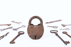 Oud roestig die hangslot met inzameling van sleutels op witte achtergrond worden geïsoleerd Stock Foto's