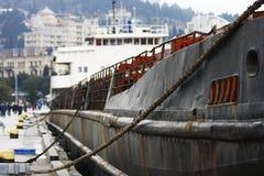 Oud roestig die vrachtschip bij burgerlijke haven wordt vastgelegd Het oude schip concept van de recyclingsnoodzaak stock afbeeldingen